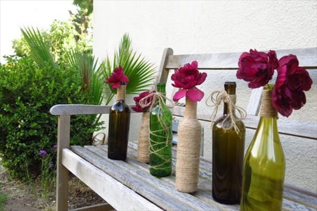 For an outdoor party or event you can also use wine bottles as vases for the fence. Tie twine around them, put a rose inside and decorate the walls and fences with them.