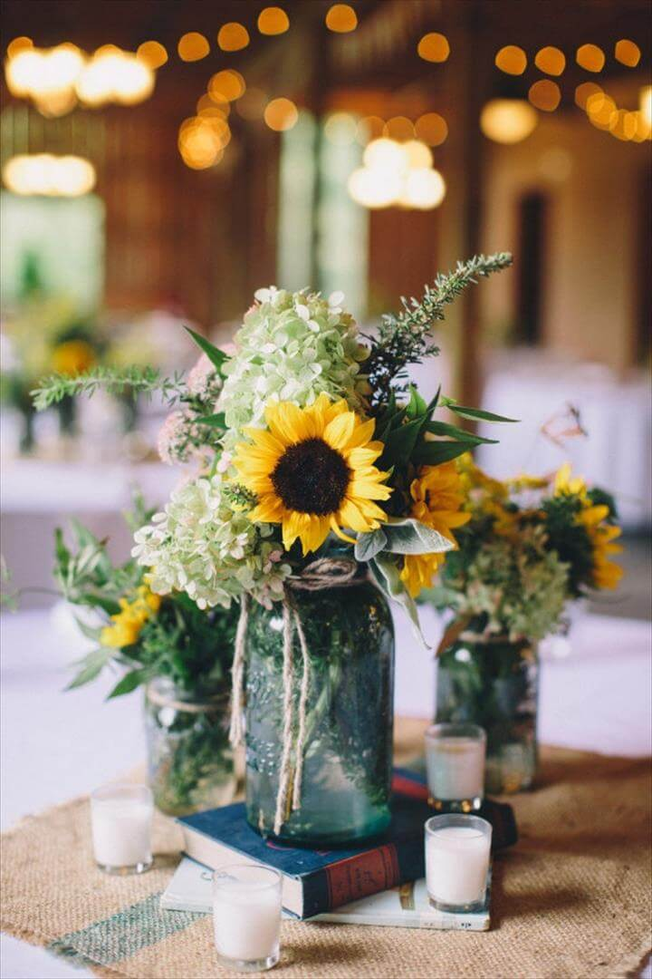 centerpieces with burlap square, aqua mason jars and books