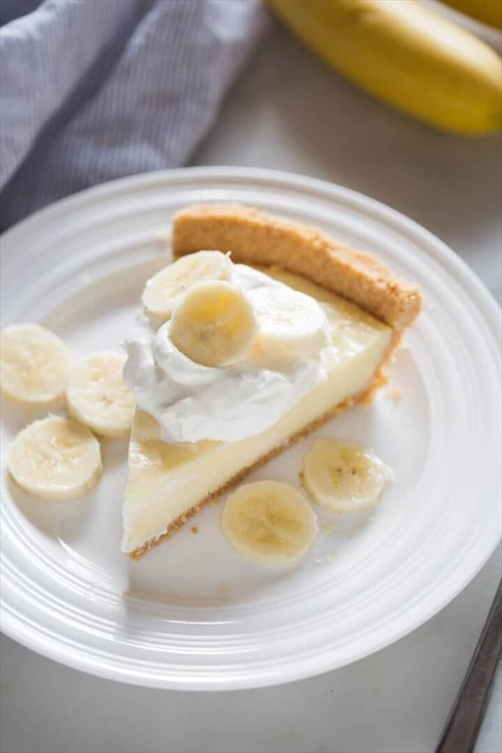 Banana Cream Pie Slice On A White Plate with Fresh Banana Slices On Top of Whipped